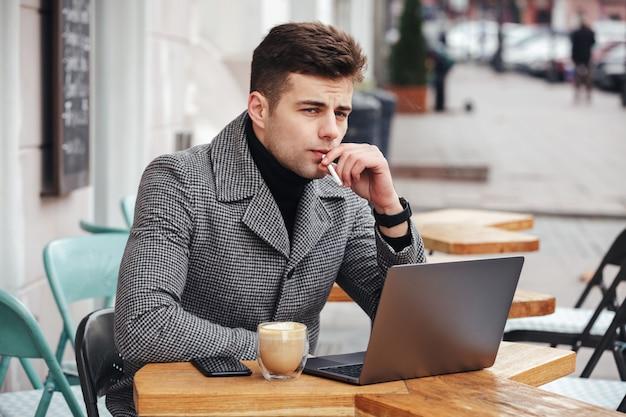 Cara caucasiano bonito com olhar pensativo sentado no café lá fora, fumando cigarro e bebendo cappuccino