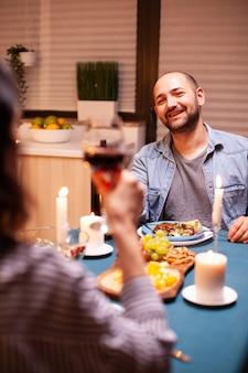 Cara celebrando relacionamento na cozinha com esposa feliz segurando um copo de vinho tinto, caminhando feliz sentado à mesa da sala de jantar, desfrutando da refeição em casa, tendo um tempo romântico à luz de velas