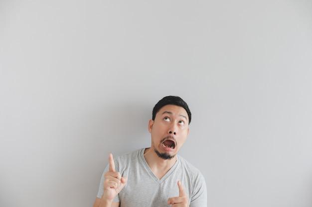 Cara chocada do homem no t-shirt cinzento com ponto da mão no espaço vazio.