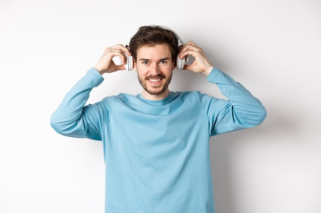 Cara colocou fones de ouvido sem fio para ouvir música ou podcast, sorrindo para a câmera, em pé sobre um fundo rosa.