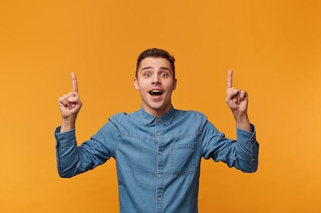 Cara com a boca aberta de surpresa mostra com os dedos indicadores