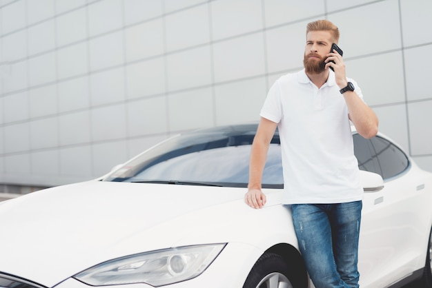 Cara com barba falando no telefone perto de seu carro elétrico.