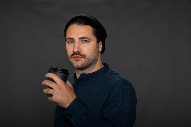 Cara com barba por fazer, bigodudo, com boné de malha posando com uma xícara de café descartável