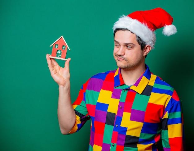 Cara com chapéu de natal e camisa vintage segurando uma casa de brinquedo no verde