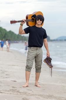 Cara com pé de guitarra na praia, calças cargo