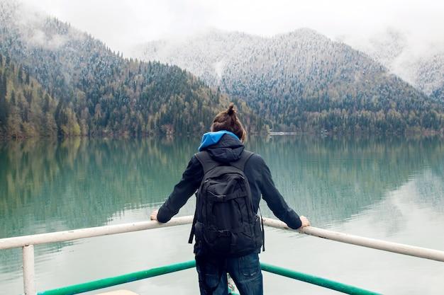 Cara com rabo de cavalo, usando mochila e jaqueta, fica para trás e olha para o lago ritsa na manhã de primavera