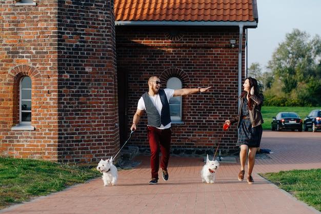 Cara com sua namorada correndo ao longo da rua com seus animais de estimação