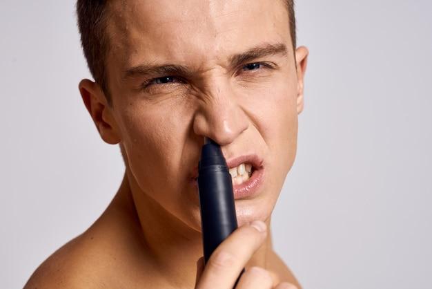 Cara com um aparador na mão removendo o cabelo do nariz, ombros nus, emoções leves