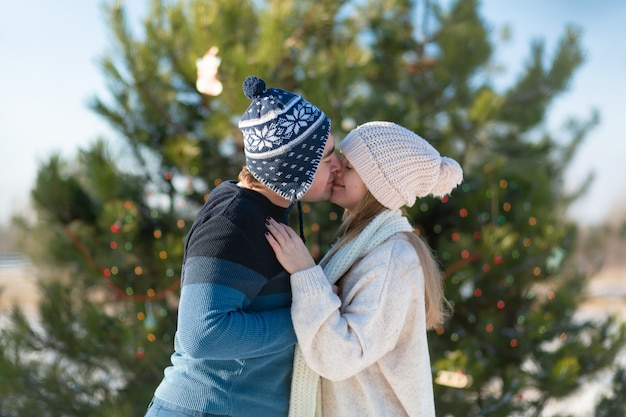 Cara com um beijo de menina em uma árvore de natal verde decorada com brinquedos festivos e guirlandas no inverno na floresta. romance de inverno