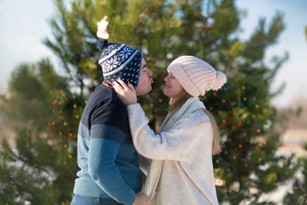 Cara com um beijo de menina em uma árvore de natal verde decorada na floresta