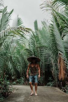 Cara com um chapéu de palha em ambiente tropical