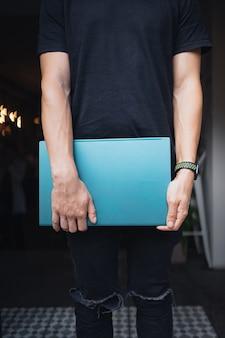 Cara com um laptop fechado na mão, dentro de casa