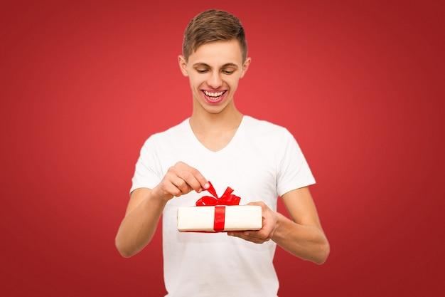 Cara com um presente em um fundo vermelho, retrato de um cara em um fundo vermelho com um lugar sob a inscrição