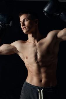 Cara com um torso bombeado gesticulando com as mãos em um atleta de fitness de luvas de boxe de fundo preto. foto de alta qualidade