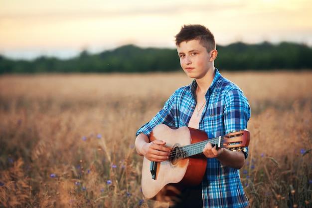 Cara com um violão tocando músicas na natureza por do sol