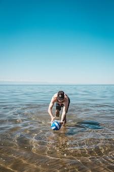 Cara com uma bola de vôlei no mar num dia de verão.