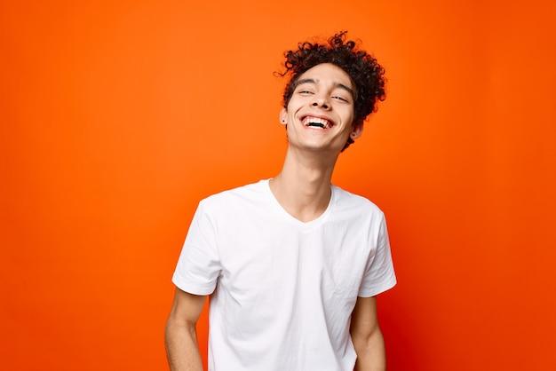 Cara com uma camiseta branca gesticulando com a mão sobre um fundo laranja