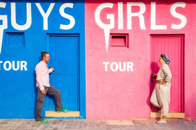 Cara com uma garota perto de uma parede engraçada incomum. o conceito de diferenças de gênero.