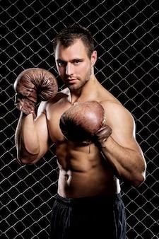 Cara com uma luvas de boxe, mostrando os músculos na cerca