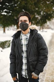 Cara com uma máscara. índio com roupas quentes. homem na rua no inverno.