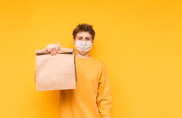 Cara com uma máscara médica e com um saco de papel posa em um amarelo e oferece comida a partir da entrega. pandemia do coronavírus.