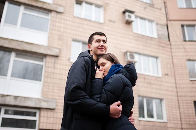 Cara com uma mulher se abraçando na rua