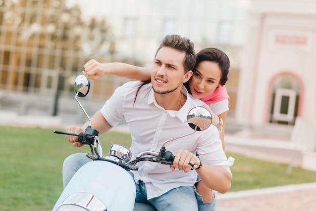 Cara concentrado com barba dirigindo scooter em um dia quente de outono
