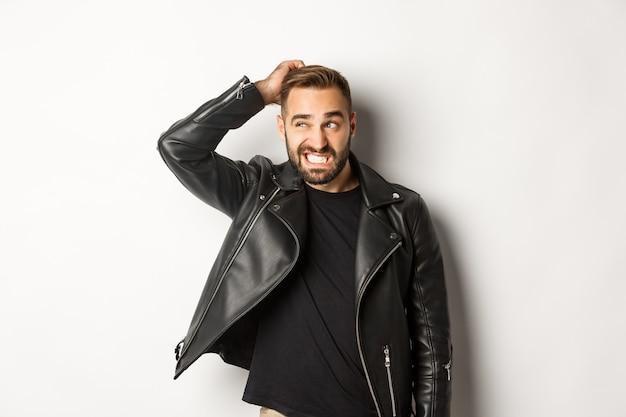Cara confuso em uma jaqueta de couro preta parecendo estranho e inseguro, coçando a cabeça intrigado e olhando para a esquerda
