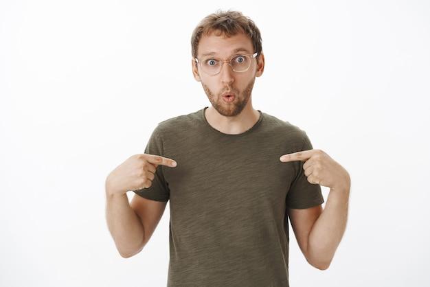 Cara criativo surpreso e maravilhado com cerdas nos óculos e camiseta verde-escura apontando para si mesmo, dobrando os lábios de interesse e curiosidade sendo escolhido pelo chefe