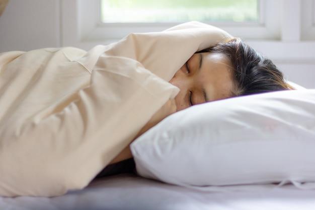Cara da jovem mulher que dorme ao encontrar-se na cama branca no alvorecer do raio de sol.