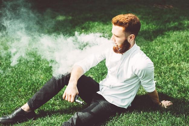 Cara de 20 anos em uma camisa branca, sentado na grama e vaping.