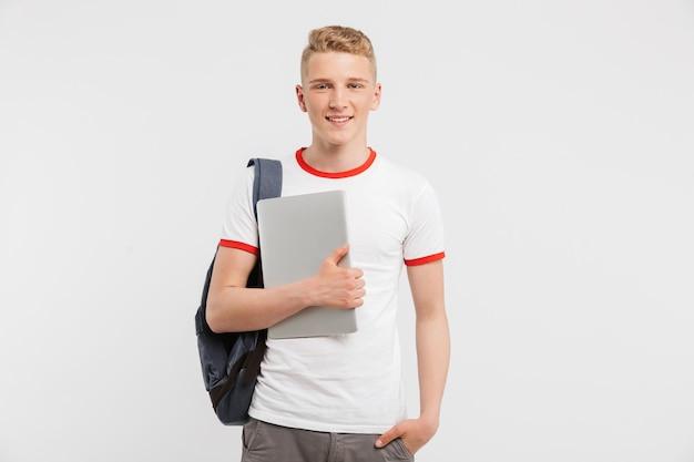Cara de adolescente 16-18 anos de idade vestindo roupas casuais e mochila, olhando para você com segurando o laptop na mão, isolado sobre o branco