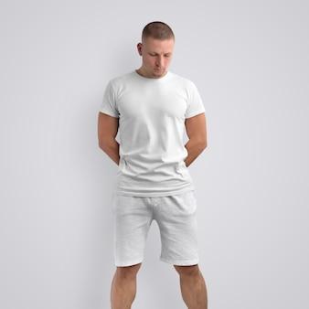 Cara de ajuste atraente em uma camiseta em branco e shorts cinza de malha em um fundo branco do estúdio. pose frontal. o modelo pode ser usado em seu design.