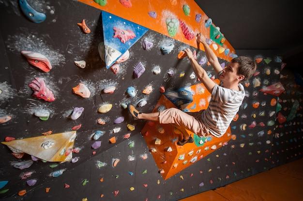 Cara de alpinista escalando a pedra artificial no ginásio