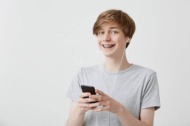 Cara de cabelo loiro, vestindo camiseta cinza segurando o telefone inteligente moderno usando a conexão de internet de alta velocidade, mensagens de texto para seus amigos, sorrindo amplamente. comunicação e tecnologia moderna.