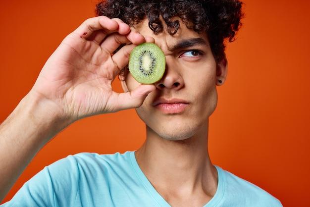 Cara de camiseta azul kiwi segurando frutas vermelhas do estúdio