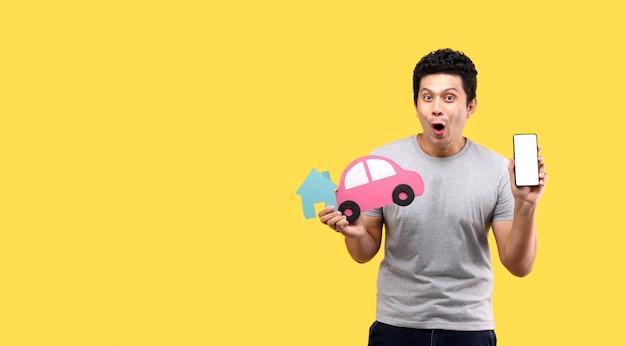 Cara de choque e surpresa do homem asiático, segurando o carro de papel e forma de casa de papel, apresentando telefone inteligente isolado na parede amarela
