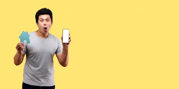 Cara de choque e surpresa do homem asiático segurando papel casa forma apresentando telefone inteligente isolado na parede amarela