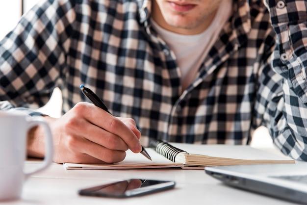 Cara de close-up, escrevendo no caderno