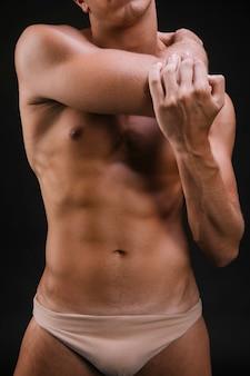 Cara de colheita aquecendo o músculo do braço