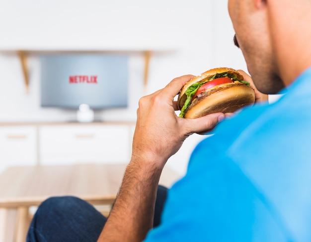 Cara de colheita comendo hambúrguer e assistindo programas de tv