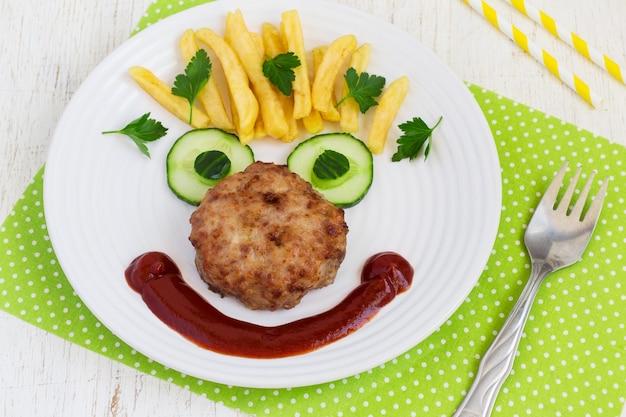 Cara de comida engraçada com uma costeleta, batatas fritas e pepino
