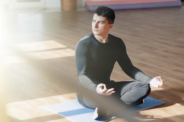 Cara de esportes atraente fazendo yoga. sala de sol e sombras. academia e esportes.