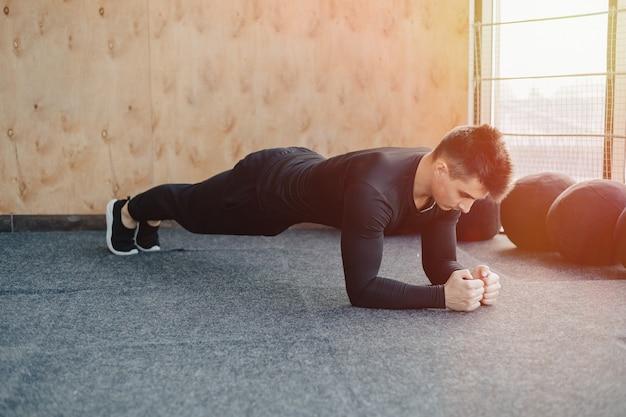 Cara de esportes fazendo exercício de prancha. academia e esportes. estilo de vida saudável.