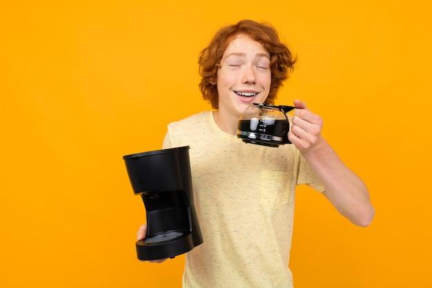 Cara de estudante com uma máquina de café bebe café de uma caneca de vidro e aprecia o aroma em uma parede amarela