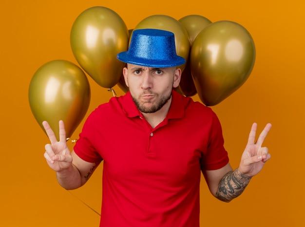 Cara de festa jovem bonito carrancudo usando chapéu de festa em pé na frente de balões, olhando para a frente, fazendo um gesto de paz isolado na parede laranja