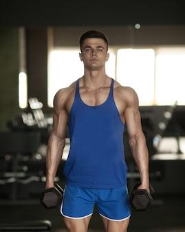 Cara de fisiculturista muscular fazendo exercícios com halteres na academia