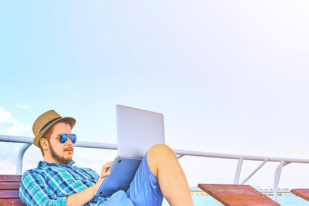 Cara de freelancer encontra-se em uma espreguiçadeira e funciona em um laptop com óculos escuros e chapéu