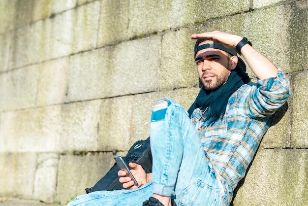 Cara de hippie sentado no chão ao ar livre.