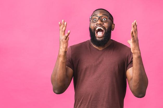 Cara de homem afro-americano espantado surpreso em casual isolado no retrato de estúdio de fundo rosa. conceito de estilo de vida de pessoas. simule o espaço da cópia. manter a boca aberta.